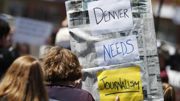 A sign from a rally against the ownership of the <em>Denver Post</em>, Alden Global Capital, in May 2018. Former <em>Post </em>journalists created <em>The Colorado Sun </em>that year; now <em>The Sun</em> has acquired two dozen suburban Denver papers.