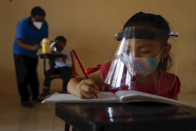 Wearing a mask and a face shield to curb the spread of the coronavirus, 10-year-old Jade Chan Puc writes in her workbook during the first day of class in Hecelchakán, Campeche state, Mexico, on April 19. On average, schools in Latin America and the Cari