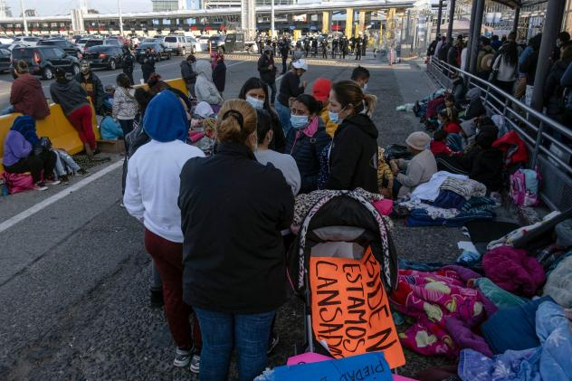 Migrants and asylum seekers are seen after spending the night in one of the car lanes off the San Ysidro Crossing Port on the Mexican side of the U.S.-Mexico border in Tijuana on April 24, 2021. A group of migrants asked U.S. migration authorities to all