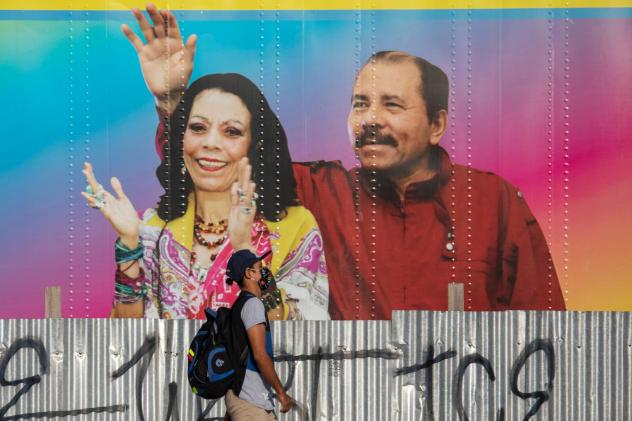 A man walks by a mobile health clinic displaying a picture of Nicaraguan President Daniel Ortega (right) and his wife and vice president, Rosario Murillo, in Managua on April 14, 2020. The government claims to be successfully combating the pandemic but h
