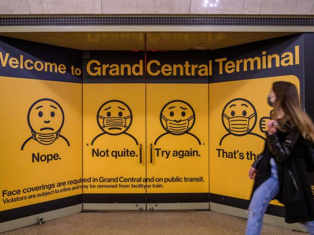 A woman walks past posters explaining mask requirements at Grand Central Terminal train station in New York City on Wednesday. Rules requiring masks on transit are unchanged by the Centers for Disease Control and Prevention's updated mask guidance for fu