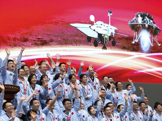 In this photo released by Xinhua News Agency, members at the Beijing Aerospace Control Center celebrate after China's Tianwen-1 probe successfully landed on Mars, at the center in Beijing, Saturday, May 15, 2021.