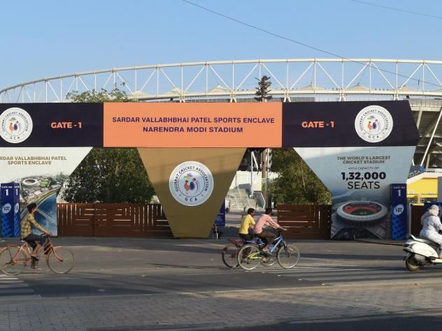 Cyclists cycle past the main entrance of the Narendra Modi Stadium in Ahmedabad, India, a venue where cricket matches were taking place during the 2021 Indian Premier League — until it was suspended.
