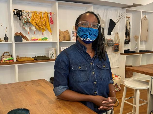 Nicole McGrew, wearing a mask by the designer N'omose Couture, says she'll require customers to mask up in her store for a short time longer.