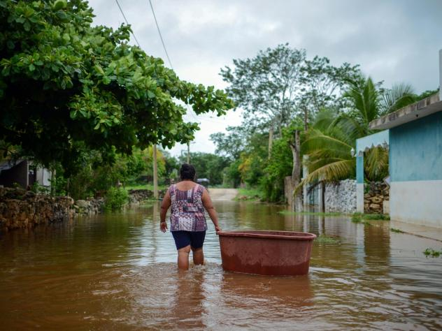 A woman from the Mayan community of Tecoh wades through the water in a flood caused by Tropical Storm Cristobal in the town of Tecoh, near Merida in Yucatan State, Mexico, in June 2020.