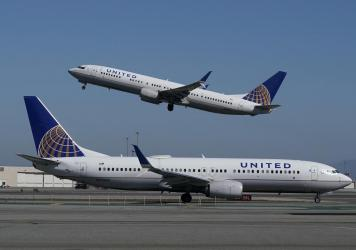A United Airlines airplane takes off over a plane on the runway at San Francisco International Airport. The company is offering vaccinated customers the chance to win free flights for a year.