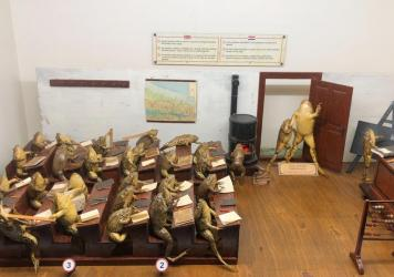 A Froggyland diorama shows a teacher trying to control a class in which students are hitting each other with rulers, arriving late to class and balancing pencils on their noses. Each  diorama displays anthropomorphized frogs in human scenes of the early