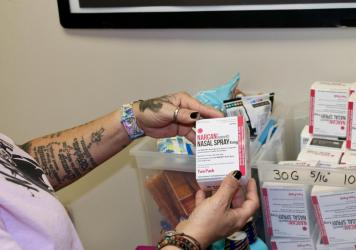 Kelly Hans holds a box of Narcan nasal spray at the county's One-Stop Shop in Austin.
