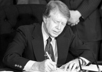 President Jimmy Carter signs emergency natural gas legislation in the Oval Office of the White House in Washington, D.C., on Feb. 2, 1977. An oil crisis contributed to a period of double-digit inflation in the 1970s.