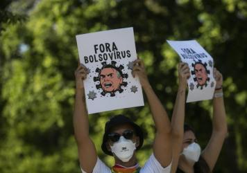 Demonstrators wearing protective face masks hold signs depicting President Jair Bolsonaro as a virus protest against the government's response in combating COVID-19, demanding the impeachment of Bolsonaro, in Rio de Janeiro, Brazil, Saturday, May 29, 202