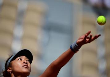 Japan's Naomi Osaka eyes the ball as she serves during the first round of the French Open tennis tournament Sunday in Paris.