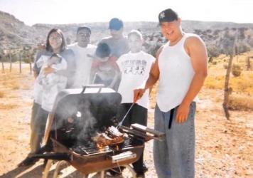 Carlos Yazzie (right) grills with his family. After he was arrested, he was left unmonitored for six hours and died of acute alcohol poisoning.
