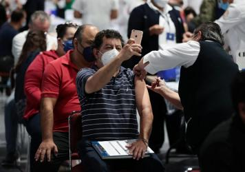A man takes a selfie while getting the COVID-19 vaccine during a vaccination day in Mexico City.