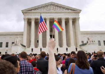 A man holds a U.S. and a rainbow flag outside the Supreme Court in Washington, D.C., on June 26, 2015, after the court legalized gay marriage nationwide.