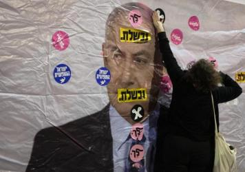 """An Israeli protester places a sticker on a banner showing Israeli Prime Minister Benjamin Netanyahu during a demonstration outside the prime minister's residence in Jerusalem on June 5. The Hebrew reads: """"You failed"""" and """"Leave."""""""