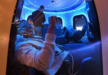Participants sit a Blue Origin space simulator during a conference on robotics and artificial intelligence in Las Vegas on June 5, 2019. On Saturday, Blue Origin announced that an unidentified bidder will pay $28 million for a suborbital flight on the co
