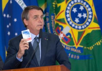 """Brazilian President Jair Bolsonaro holds up a box of chloroquine, an antimalarial medicine that his administration endorsed as part of an """"early treatment"""" strategy for COVID-19. There is no evidence the drug can prevent the coronavirus or reduce the sev"""