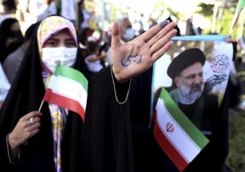 """A supporter of presidential candidate Ebrahim Raisi shows her hand with writing in Persian that reads """"Raisi,"""" during a rally in Tehran, Iran, Wednesday. He is the country's hard-line judiciary chief and is closely aligned with Supreme Leader Ayatollah A"""