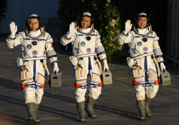 Chinese astronauts, from left, Tang Hongbo, Nie Haisheng, and Liu Boming wave as they prepare to board for liftoff Thursday at the Jiuquan Satellite Launch Center in Jiuquan in northwestern China. China plans to launch three astronauts onboard the Shenzh