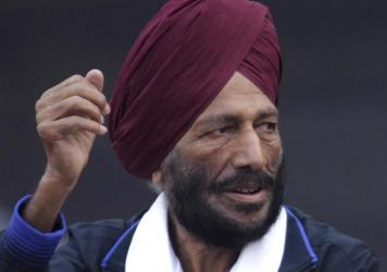 In this Dec. 15, 2013, file photo, former Indian athlete Milkha Singh, with, and Bollywood actor Bipasha Basu waves to the participants during the Delhi Half Marathon in New Delhi, India.