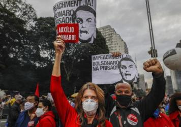 """Demonstrators hold signs that read in Portuguese: """"Impeachment now! Bolsonaro in prison"""" during a protest against Brazilian President Jair Bolsonaro and his handling of the COVID-19 pandemic, in Sao Paulo, Brazil, on Saturday."""