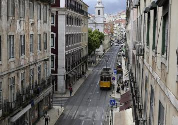 A tram drives through an empty downtown Lisbon, Portugal, on Friday. Portuguese<em> </em>authorities banned all weekend travel in and out of the capital to cut down on any further spread of the coronavirus to other parts of the country.