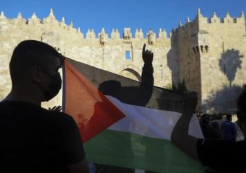 Demonstrators wave the Palestinian flag during a protest in Damascus Gate, just outside Jerusalem's Old City on June 19. Palestinians and Jewish settlers hurled stones, chairs and fireworks at each other in a tense Jerusalem neighborhood, where settler g