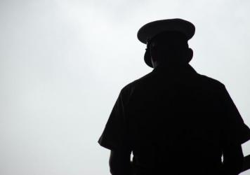 Silhouette of a United States Marine praying, photographed from behind.