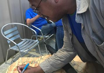 Marcellus Cadd signing his name in Round Rock, Texas, after finding a cache in all 254 counties in the state.