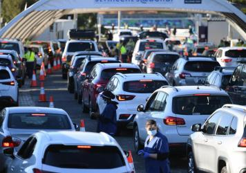 People line up in their cars to get tested for COVID-19 at a pop-up testing clinic at Bondi Beach in Sydney on Friday. Parts of Sydney will go into lockdown late Friday because of a growing coronavirus outbreak in Australia's largest city.