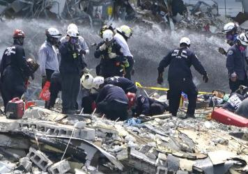 Rescue workers search the rubble of the Champlain Towers South condominium on Saturday in the Surfside area of Miami. The building partially collapsed on Thursday.