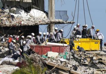 Rescue workers search for survivors in the rubble at the Champlain Towers South condo building Monday in Surfside, Fla. Some 150 people remain unaccounted for after the building partially collapsed last week.