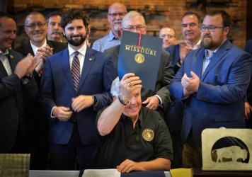 Missouri Gov. Mike Parson shows off HB85, which he signed inside Frontier Justice gun shop in Lee's Summit, Mo., on Sat., June 12. The bill prevents local and state law enforcement officials from enforcing federal gun laws.
