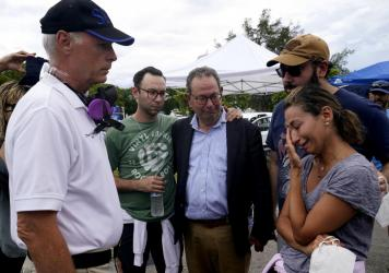Surfside, Fla., Mayor Charles Burkett (left) talks with Rachel Spiegel, whose mother is missing in the Champlain Towers South collapse.