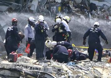 Rescue workers search the rubble of the Champlain Towers South condominium, Saturday. Search and rescue teams found another victim buried underneath the rubble on Tuesday, bringing the death toll to 12.