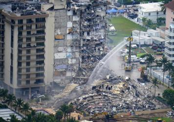 In this June 25, 2021, file photo, rescue personnel work at the remains of the Champlain Towers South condo building in Surfside, Fla.