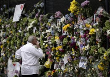 A man looks at a memorial Tuesday with pictures of some of the missing from the partially collapsed 12-story Champlain Towers South condo building in Surfside, Fla.