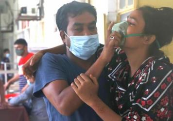 A man assists a patient with difficulty breathing at the Medical College Hospital in Rajshahi, Bangladesh, on June 16, as the delta variant of the coronavirus quickly spread.
