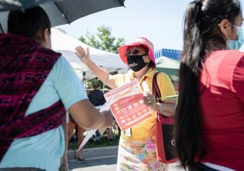 Promotora Gladis Lopez engages community members on June 23 at the Crossroads Farmers Market located at the border of Takoma Park and Langley Park, an area of suburban Maryland with a large Latino population.