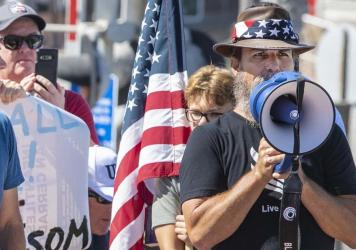 Alan Hostetter, seen here in May 2020, became a leading activist against coronavirus-related lockdown policies in Orange County, Calif. Hostetter, a former police chief and yoga instructor, is now facing conspiracy charges for his alleged role in the ins