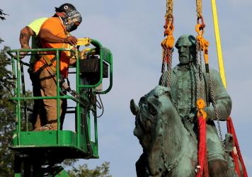 Workers remove a statue of Confederate Gen. Robert E. Lee from Market Street Park on Saturday in Charlottesville, Va.