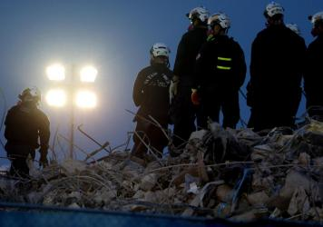 Workers oversee an excavator dig through the rubble of the collapsed 12-story Champlain Towers South condo building on Friday.