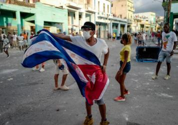 A man waves a Cuban flag during a demonstration against Cuban President Miguel Díaz-Canel's government Sunday in Havana as large numbers take part in rare protests against the communist regime.