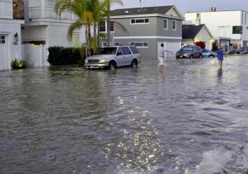 Streets and homes flooded in Newport Beach, Calif., during a high tide in July 2020. So-called sunny day floods are getting more common in coastal cities and towns as sea levels rise due to climate change.