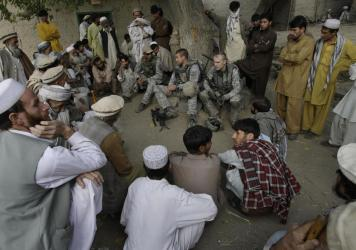 An American lieutenant, center, meets with villagers in Afghanistan's Kunar province in 2009, assisted by an interpreter, sitting to his right wearing a baseball cap. The U.S. will begin the evacuation of some 18,000 Afghan nationals who aided military o
