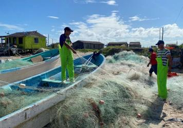 Mexican fishermen tend to their nets on Bagdad Beach, just south of the Texas-Mexico border. Red snapper poaching along the Gulf is a multi-million dollar black market.