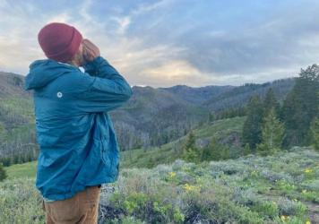 Logan Miller, a field technician for the Wood River Wolf Project, conducts a howling survey to try to locate wolf packs in the valley. (Rachel Cohen/Boise State Public Radio)