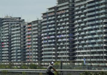 A man rides a bike near the village for the Summer Olympics in Tokyo. On Saturday, officials announced the first case of COVID-19 found at the center housing thousands of athletes.