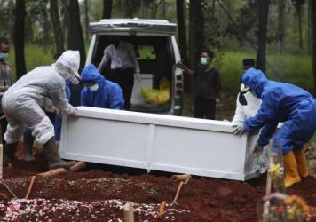 Workers in protective suits carry a coffin containing the body of a COVID-19 victim to a grave for burial at the Cipenjo Cemetery in Bogor, West Java, Indonesia, Wednesday, July 14, 2021.
