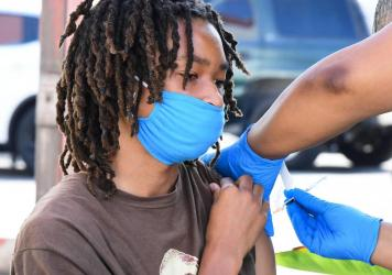 COVID-19 cases across the U.S. are rising in all 50 states as the delta variant of the coronavirus spreads. Here, a teenager receives a COVID-19 vaccine on July 16 at a mobile vaccine clinic hosted by Mothers in Action and operated by the Los Angeles Cou